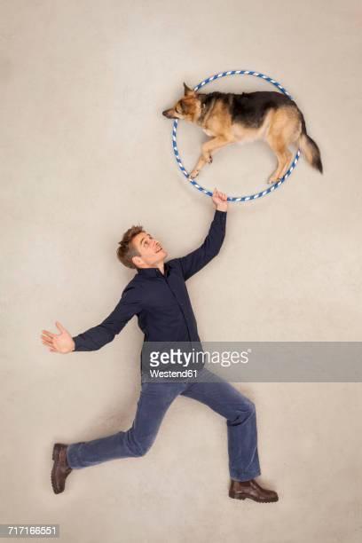 Man training his dog to jump through a hoop