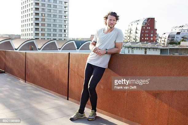Man training, leaning against urban footbridge