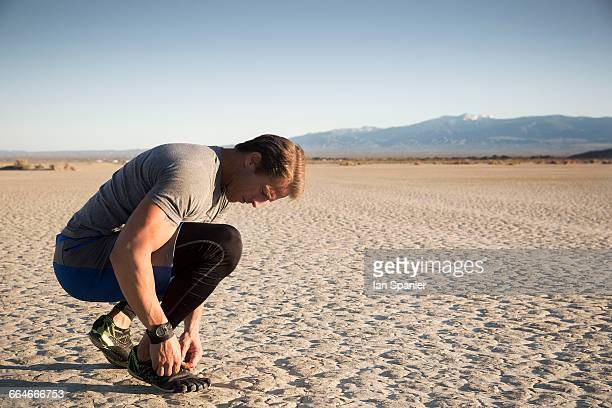 man training, tying trainer laces on dry lake bed, el mirage, california, usa - el mirage - fotografias e filmes do acervo