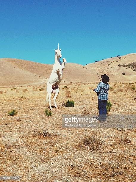 Man Training Unicorn On Field Against Clear Blue Sky