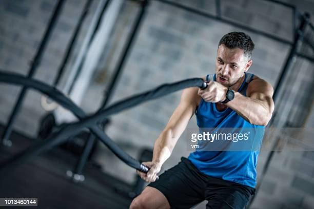 man training with battle ropes in a gym - endurance stock pictures, royalty-free photos & images
