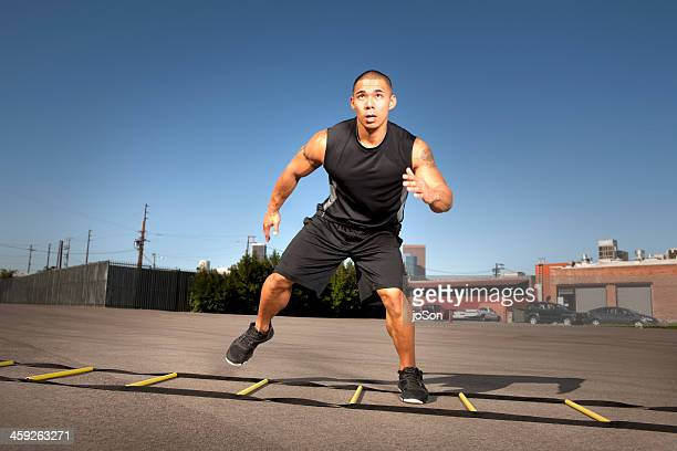 man training with soccuer agility ladder
