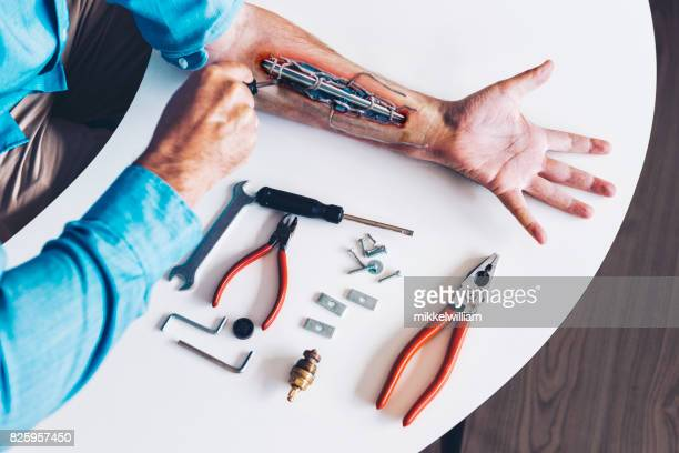 man transforms into cyborg by implanting machine parts into robotic arm - transplant surgery stock photos and pictures