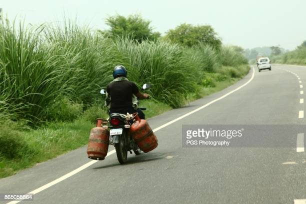 Man transporting 2 cooking gas cylinders on his little bike