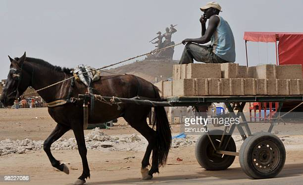 A man transporting bricks on a horse cart drives past the 'African Renaissance Monument' on April 1 2010 in Dakar during preparations for the April 3...