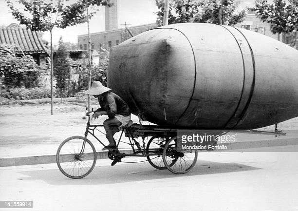 A man transporting on a bicycle a big methane container to refuel Beijing buses Beijing 1961