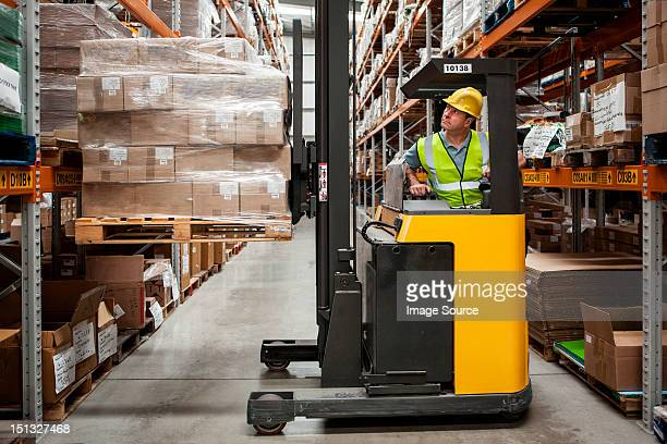 Man transporting stock in distribution warehouse