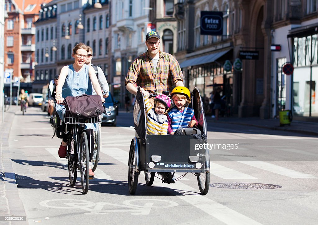 Man transporting two children on a bicycle fitted with box : Stock Photo