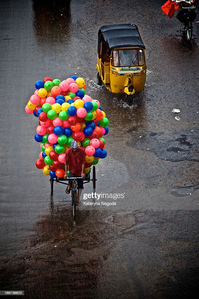 CONTENT] A man transports colorful balloons on his bike in