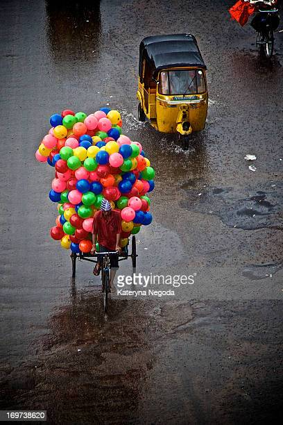 CONTENT] A man transports colorful balloons on his bike in the rain Old city market in Hyderabad India
