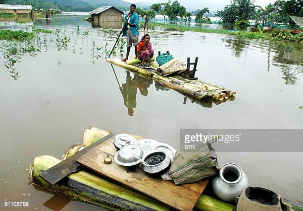 Man transports his wife and some belongings on a makeshift raft through flood waters after their house was submerged, 23 July 2004 in the...