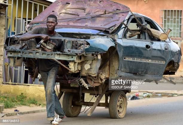 A man transports the carcass of a car on a twowheeled carriage in a neighborhood in Abobo a suburb of Abidjan on December 1 2017 / AFP PHOTO / ISSOUF...