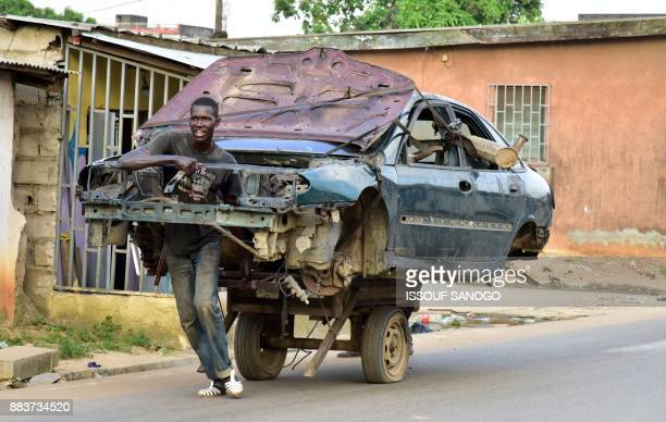 TOPSHOT A man transports the carcass of a car on a twowheeled carriage in a neighborhood in Abobo a suburb of Abidjan on December 1 2017 / AFP PHOTO...