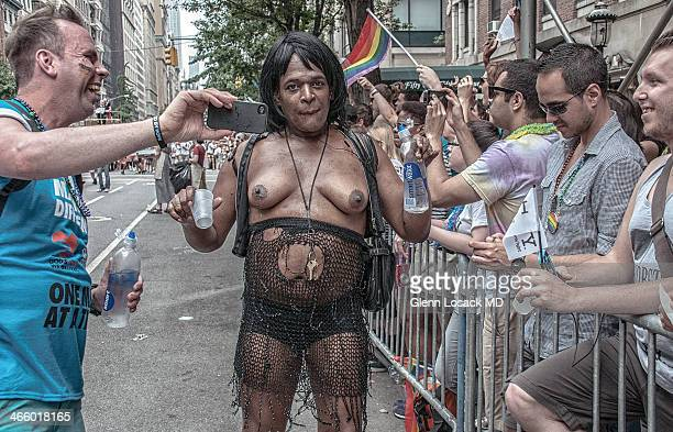 Man, transvestite or transsexual baring breasts walks the Gay parade in Manhattan with crowd. One man taking his photo. Manhattan, New York USA