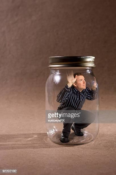 Man trapped in mason jar looking out (Concept Series)