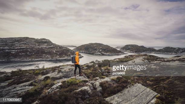 man travel adventures: mountain hiking in norway - yellow coat stock pictures, royalty-free photos & images