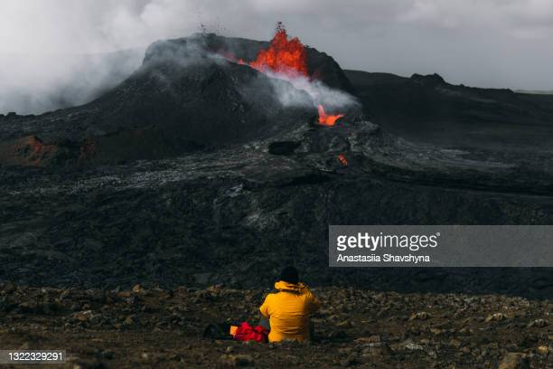 man traveler feeling awe looking at fagradalsfjall volcanic eruption in iceland - iceland stock pictures, royalty-free photos & images