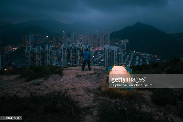 man traveler taking photo on top of mountains near of tent camping - country geographic area stock pictures, royalty-free photos & images