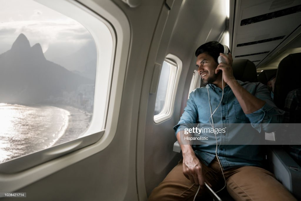 Man traveling by plane and listening to music : Stock Photo