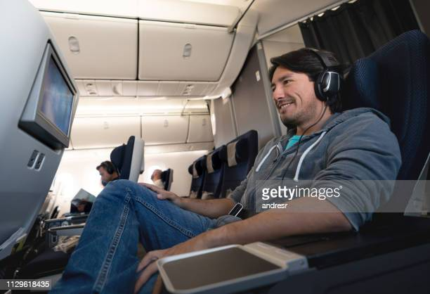man traveling by plane watching in-flight entertainment using earphones - arts culture and entertainment stock pictures, royalty-free photos & images