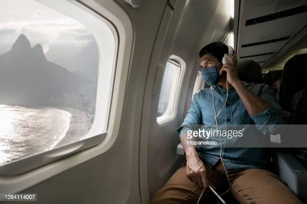 homem viajando de avião usando máscara facial e olhando para o rio pela janela - turismo urbano - fotografias e filmes do acervo