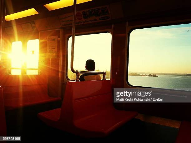 Man Traveling By Train At Sunset