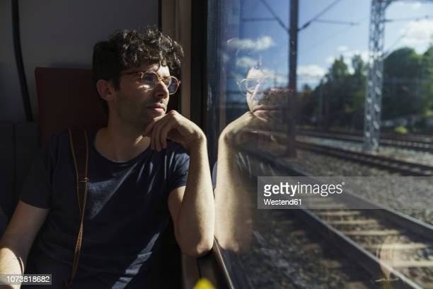 man traveling by train looking out of window - passenger train stock pictures, royalty-free photos & images