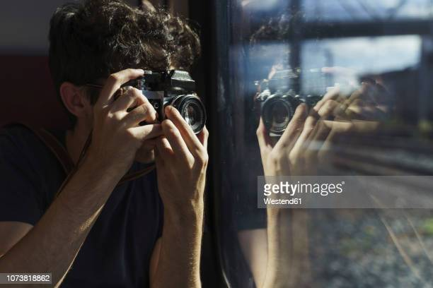 man traveling by train taking picture with old-fashioned camera - photographe photos et images de collection