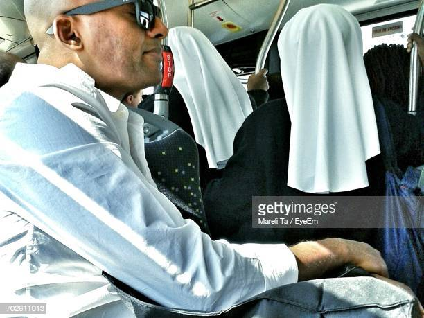 man traveling in bus with nuns in background - nun stock pictures, royalty-free photos & images