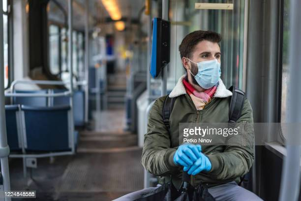 man travelling alone in the empty city tram during covid-19 quarantine - public transportation stock pictures, royalty-free photos & images