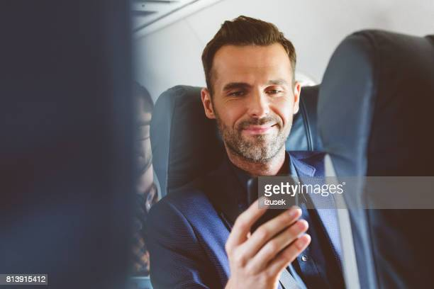 man travelling by plane and using mobile phone - aeroplane stock pictures, royalty-free photos & images