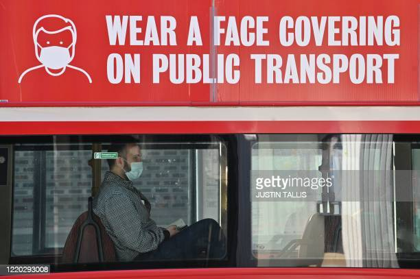 A man travels on a bus wearing a face mask in central London on June 16 2020 after face coverings became mandatory on public transport to ward...