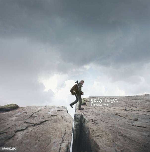 Man trekking, crossing chasm in mountains