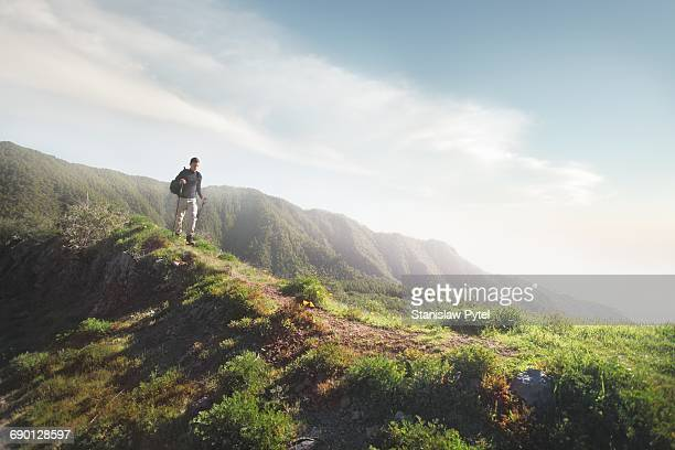 Man trekking on grassy road in mountains