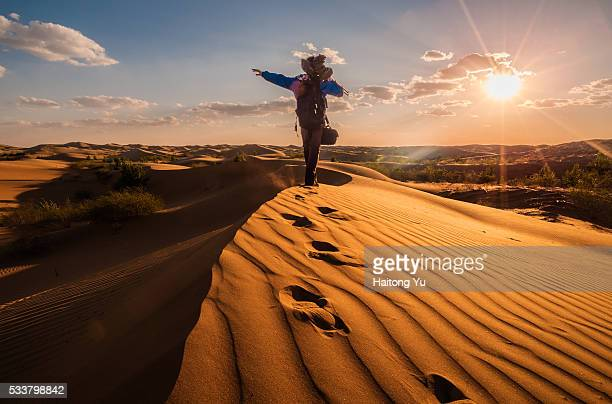 Man (Chinese aged 24) trekking on ridge of sand dunes with camera and tripod