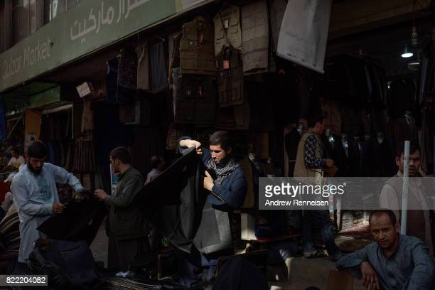 A man tries on a jacket in a bazaar in Kabul's old city neighborhood on July 20 2017 in Kabul Afghanistan Despite a heavy security presence...