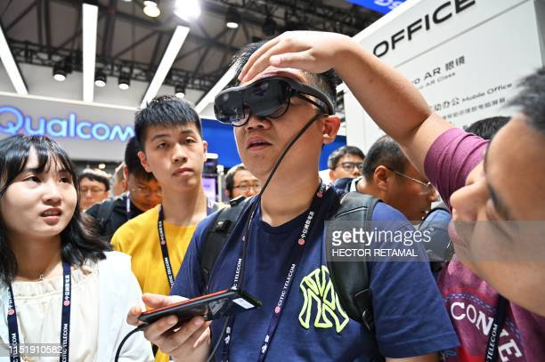 A man tries out an augmented reality headset during the Mobile World Congress introducing nextgeneration technology at the Shanghai New International...