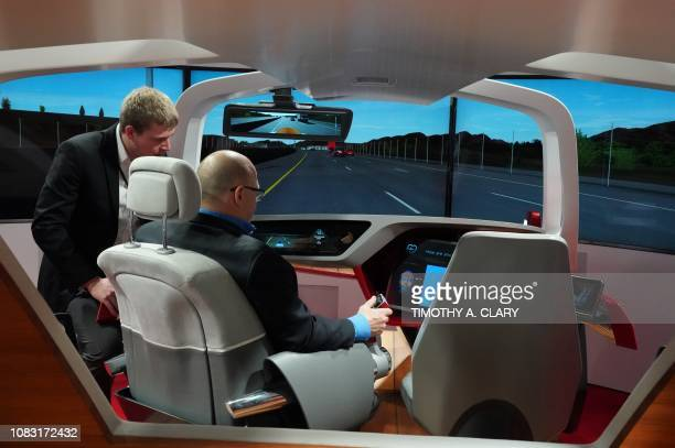 A man tries out an autonomous car simulator from BCS Automotive Interface Solutions during day two of the 2019 The North American International Auto...