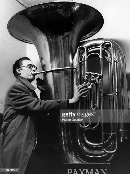 A man tries out an outsize sub contra bass tuba found in the basement of Paxman Brothers the Soho instrument makers It contains 34 feet of piping