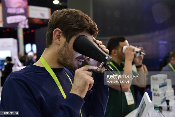 A man tries out the EyeQue Insight home visual acuity screener at the Sands convention hall during CES 2018 in Las Vegas on January 9 2018 / AFP...