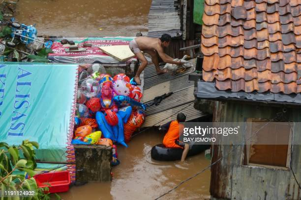 Man tries to capture his goose from the roof of their home as they evacuate after rain all night caused local flooding in certain areas in Jakarta on...