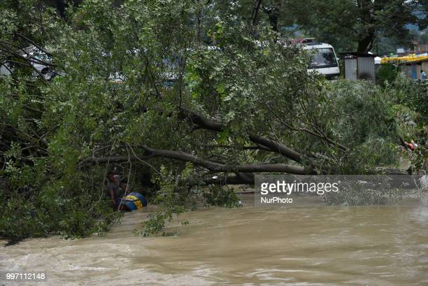Man tries to carry his belonging in a flood water overflowed from River affected due to incessant rainfall at Thimi, Bhaktapur, Nepal on Thursday,...