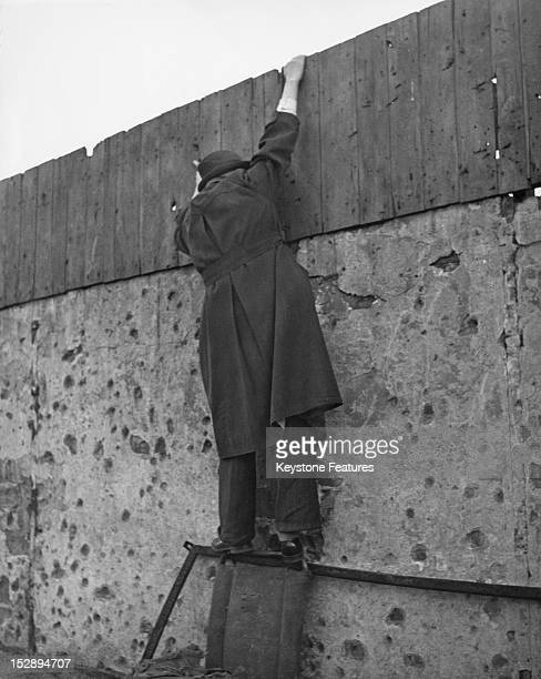A man tries to catch a free glimpse of a sports event in Berlin December 1950 High taxation on seats has made legal attendance too expensive for many