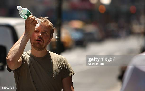 Man tries to cool himself with a bottle of water during the first heat wave of the year June 9, 2008 in New York City. According to the National...