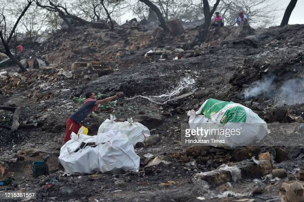 A man tries to douse the smoke at the fire site in which around 1000 shanties burnt down and turned into ashes on Monday night at Tughlakabad...