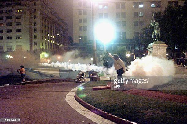 A man tries to escape tear gas thrown by police to disperse demonstrators at the Plaza de Mayo in Buenos Aires 20 December 2001 The police action...