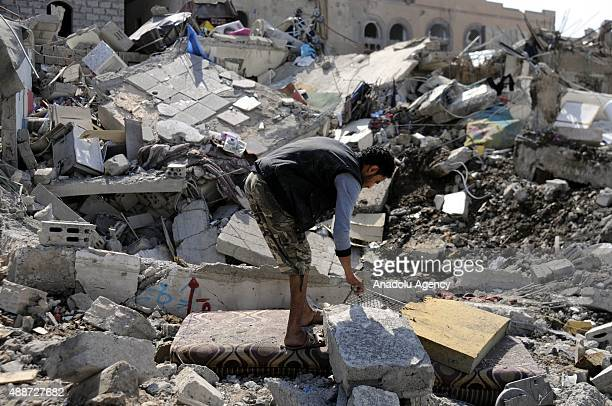 A man tries to find his belongings among the debris of his house after a Saudiled coalition airstrike targeting Houthicontrolled residential areas in...