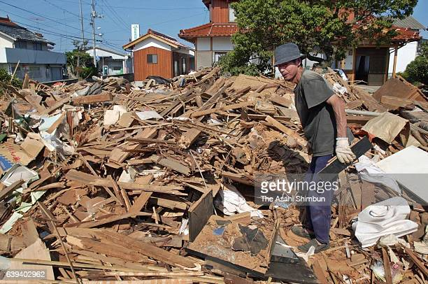 Man tries to find valuables from his collapsed home a day after the Magnitude 7.3 earthquake hit western Tottori on October 7, 2000 in Yonago,...