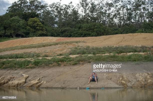 A man tries to fish on a bank dried due to the lack of rain at Funil Hydroelectric Plant reservoir in Resende about 160km west from Rio de Janeiro...