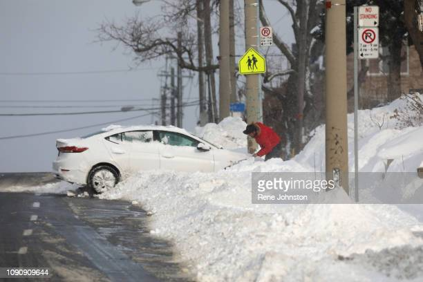Man tries to get his car out on Warden just north of Danforth rd. Nasty cold and snowy conditions made a mess of the morning commute.